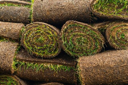 background - a stack of rolled peat rolls with grass, ready for laying  the lawn
