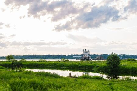 landscape of a river delta with a notch tugboat and a dredger in the background