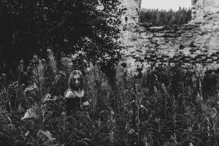 monochrome gloomy view of the ruins and woman of a zombie or witch among tall grass Archivio Fotografico