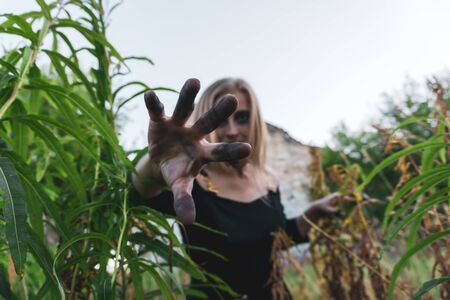 young woman cosplaying a scary witch stretches her hand with black fingers into the frame Фото со стока