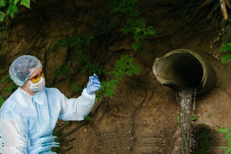 female ecologist or epidemiologist in a protective gown and mask visually evaluates test tube contents on a background of sewer coming out of the ground Stock Photo