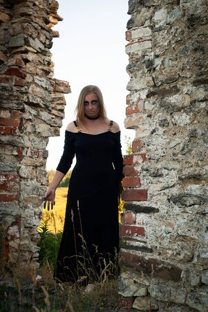 pale young woman in a black dress and scary makeup cosplay a witch among the ruins, vertical photo 写真素材