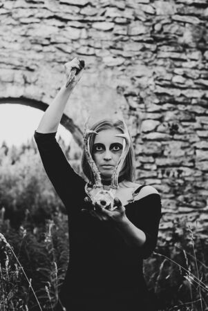 woman cosplay a witch conducting an ominous rite with a deer skull among the ruins Stok Fotoğraf