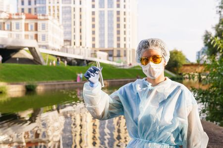 female ecologist in a protective mask looking at the camera holding a test tube with water from a city river Stockfoto - 129763499