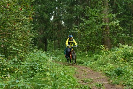 male cyclist hiker overcomes an obstacle on a trail in autumn mountain forest