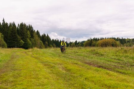 male cycling tourist on a dirt road through a field on a cloudy autumn day against the background of a distant city