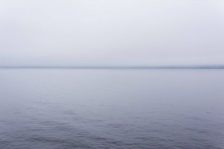 cold water surface in fog with barely visible distant shore on the horizon