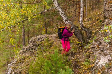 woman traveler with a backpack makes his way along a mountain trail among the autumn forest