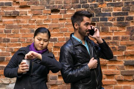 young man talking on the phone, girl misses and gestures impatience on the background of an old brick wall 版權商用圖片