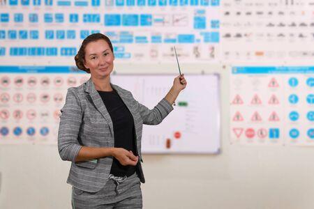 Die Ausbilderin für Verkehrsregeln lehrt die Theorie über den verschwommenen Hintergrund des Schulungsraums mit Bildern von Verkehrszeichen