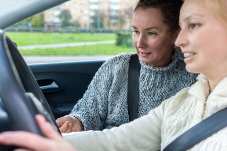 female driving instructor conducts a practical lesson with a female student