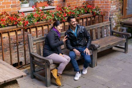 two young people a guy and a girl sitting on a bench outdoors greet someone