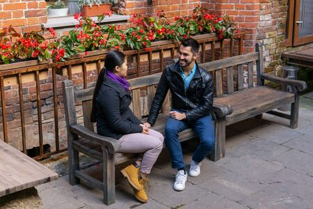two young people a guy and a girl talking sitting on a bench outdoors Stok Fotoğraf