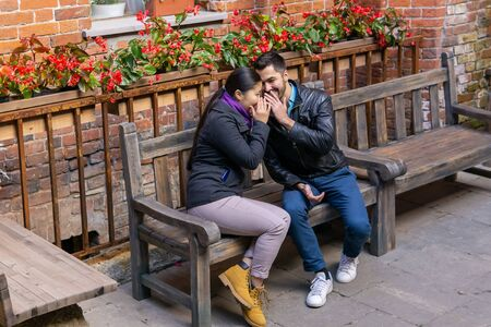 two young people a guy and a girl whisper about something and laugh sitting on a bench outdoors Stok Fotoğraf