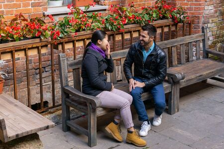 two young people a guy and a girl talking and laugh sitting on a bench outdoors