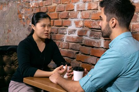two young people a guy and a girl talking about something serious while sitting at a table in a cafe on the background of a rough brick wall