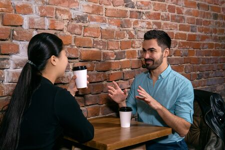 young man talks about something to a girl while they are sitting at a table in a cafe on the background of a rough brick wall