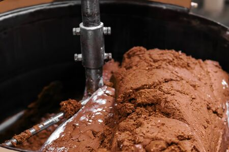 close-up of chocolate truffle filling in an industrial mixing machine