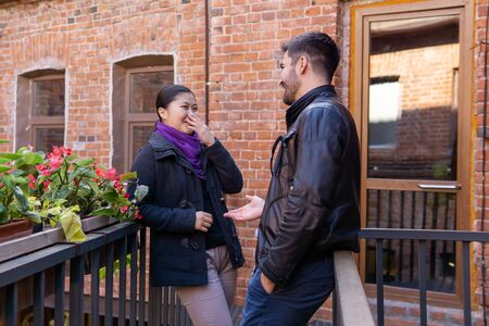 two young people a guy and a girl talking and laugh while standing on the balcony of the old building