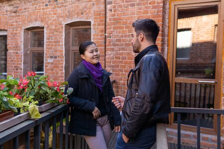 two young people a guy and a girl talking while standing on the balcony of the old building