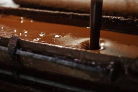 heiße geschmolzene Schokolade wird in einer Süßwarenfabrik in ein Tablett gegossen, Nahaufnahme close