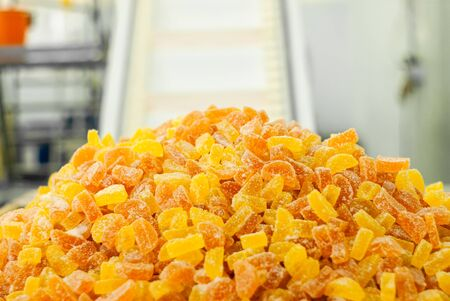 ready-made gumdrops lies on a tray at a confectionery factory against the background of a blurry interior of a workshop with a conveyor belt   版權商用圖片