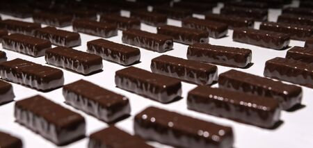 chocolates just poured with liquid chocolate on a conveyor belt of a confectionery factory close-up