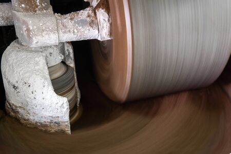 millstone of industrial melanger grind and mix cocoa and other ingredients in the process of making chocolate, blurry in motion