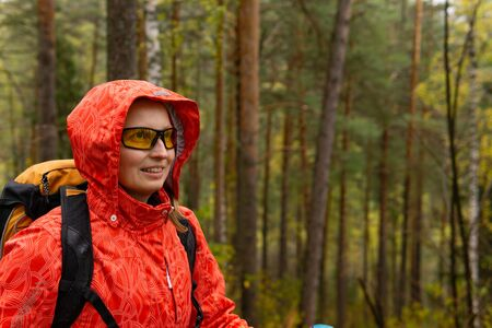 smiling young blonde female hiker with backpack in autumn forest