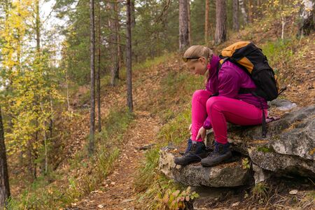 woman trekker sitting on a mountain trail and holding on to a sore ankle Stok Fotoğraf
