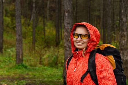 young blonde female hiker with backpack in autumn forest, half-length portrait