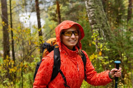 smiling woman traveler with a backpack walks through the autumn forest in rainy weather