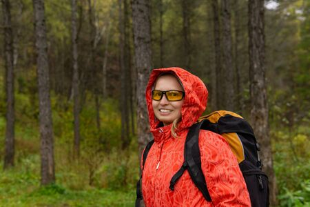 young blonde female traveler with backpack in autumn forest Stok Fotoğraf