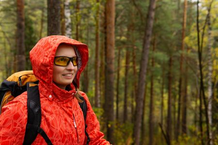 smiling young blonde female traveler with backpack in autumn forest Stok Fotoğraf