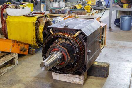 Gran motor eléctrico industrial desmontado en el proceso de reparación en el taller.