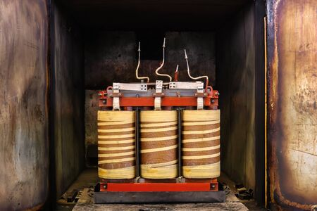 industrial transformer half pulled out of open vacuum drying oven after solidifying