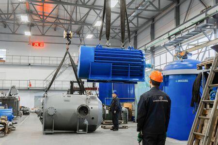 Perm, Russia - October 29, 2019: moving of huge industrial electric motors around the factory floor with bridge cranes