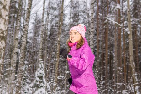 cheerful young woman jogging through winter forest Reklamní fotografie