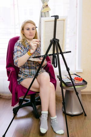 young woman artist paints something on an easel at home