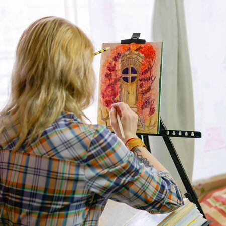 female artist illustrator creates a image on an easel