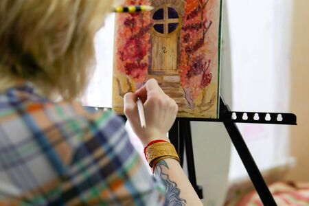 woman artist illustrator creates a picture on an easel