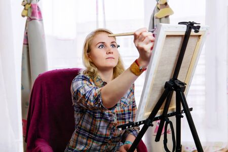 young woman artist paints with inspiration at an easel opposite the window Reklamní fotografie