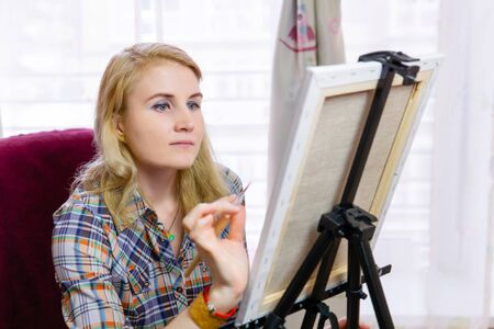 female artist makes the finishing touch in her painting