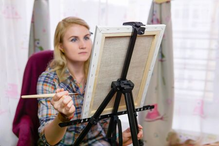 young woman artist paints at an easel opposite the window, focus on easel