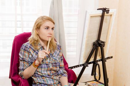 woman artist pensively looks at the canvas, pondering the art plan