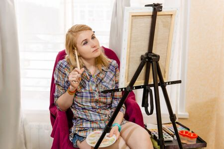 female painter with watercolor pensively looks at the canvas, pondering the art plan Reklamní fotografie