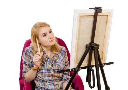 woman artist pensively looks at the canvas, pondering the art plan, on white background