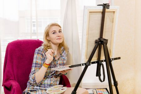woman artist with watercolor and easel looks in the frame while creating