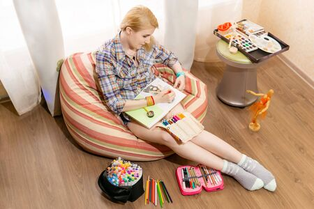 woman artist illustrator works at home makes a sketch in a notebook sitting in a bean bag chair Reklamní fotografie