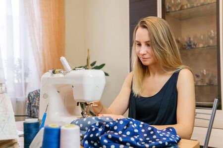 woman sews blue fabric on a sewing machine at home